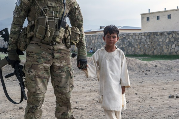 Soldier holding Afghani child's hand